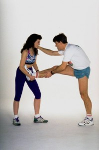 Woman helping man stretch legs