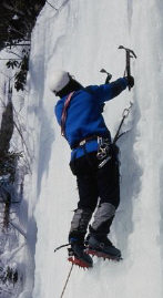 Man climbing snow covered cliff