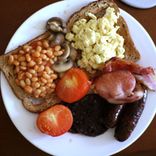 Cooked breakfast with sausage, bacon, beans, black pudding, tomato, egg, mushrooms and toast