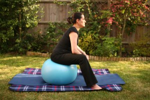 Pregnant yoga expert on swiss ball