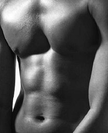 Black and white photo of a male torso showing flat stomach and abs