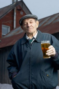 Smiling elderly man drinking glass of beer outside barn