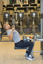 over 50 weight trainer performing a lateral pulldown