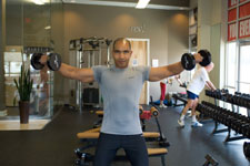 over 50 weight trainer performing dummbell lateral raises
