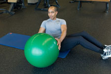 over 50 weight trainer performing a seated ball twist