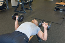 over 50 weight trainer performing a dumbbell chest press