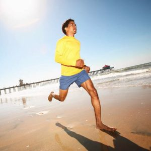 African American male running on the beach bare foot
