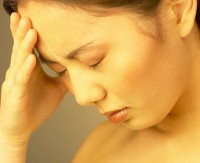 Woman with headache holding forehead in hand