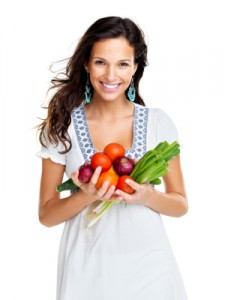 A woman holding a selection of healthy vegetables