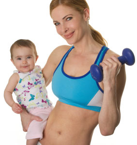 Fit mom holding her baby and a dumbbell