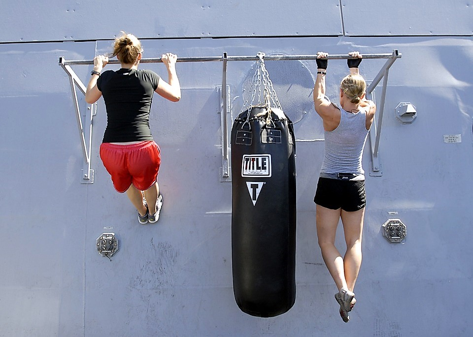 women doing pull ups alongside punch bag