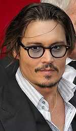 Johnny Depp with thick rimmed glasses, open collar and dark suit