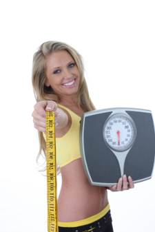 Woman wearing a yellow top, holding scales and tape measure