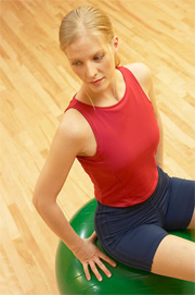 A woman in a red vest and blue shorts sitting on a green gym ball.