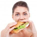 A woman eating a sub sandwich