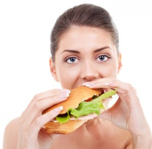 Close-up of a beautiful young woman taking a big bite of a sandwich while looking at the camera