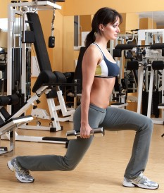 Woman doing a lunge with dumbbells
