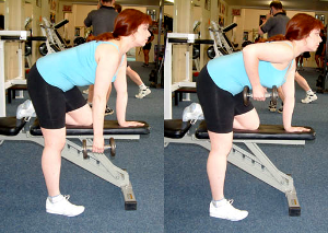 Woman performing a single arm dumbbell row, using a bench for support