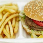 Hamburger and French fries in a fast food container