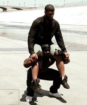 Kali squatting with man on shoulders
