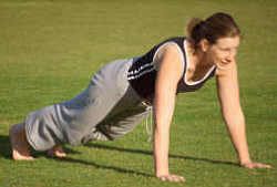 A woman doing push ups in a park