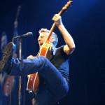 Bryan Adams kicking high on stage