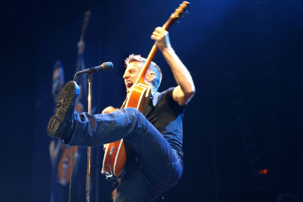 Bryan Adams kicking high on stage
