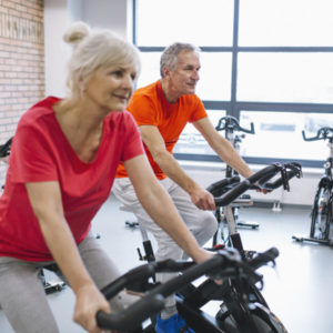 elderly couple on exercise bikes