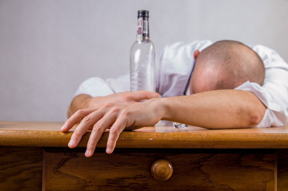 man slumped at table with empty bottle of alcohol