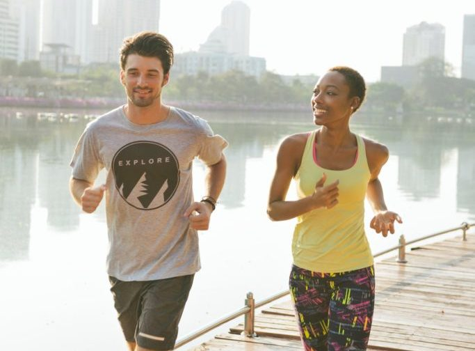 black woman and white man running along the waterside