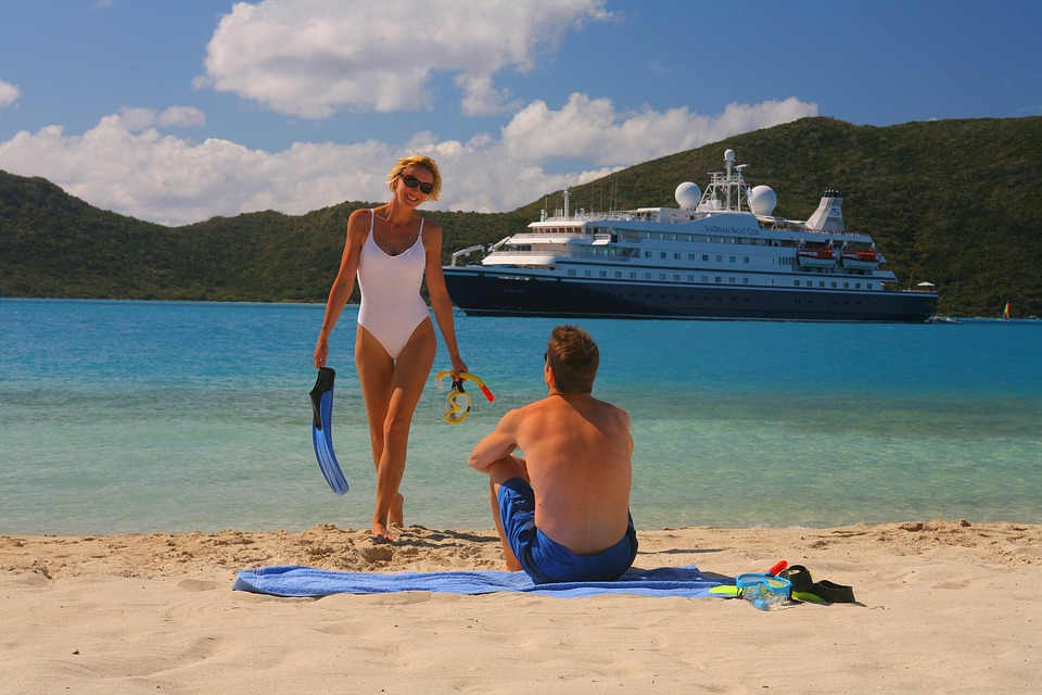 fit couple on beach with cruise liner