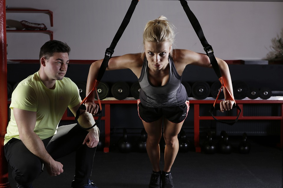 man strength training coach and woman exercising