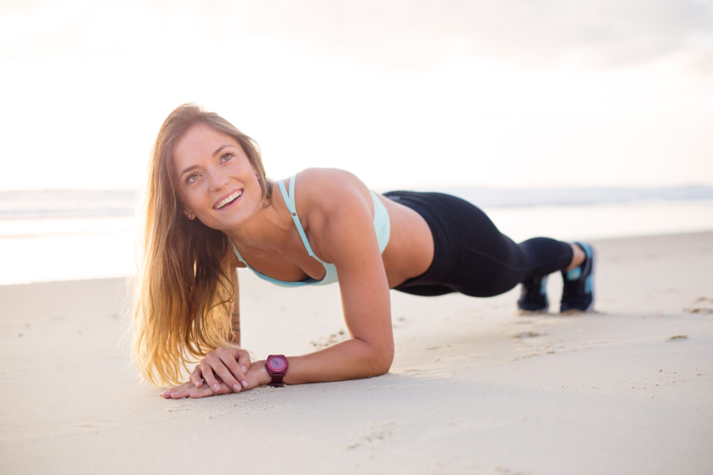 the plank performed by a woman on a beach