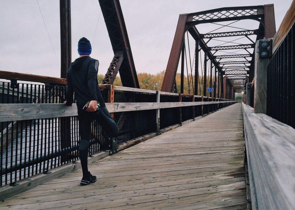 man stretching leg after running