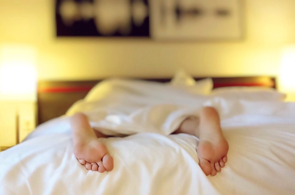 person sleeping face down on a bed