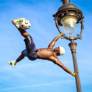 soccer player hanging on street light wth ball held on foot