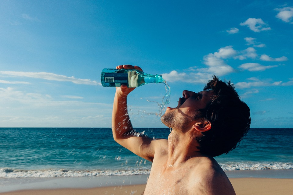 man drinking water on the beach - the water is splashing all over his face