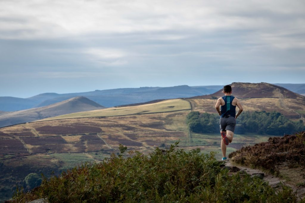 man running outside in hilly landscape