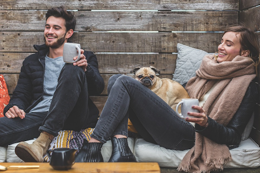 couple chating to each other in winter clothing and drinking coffee