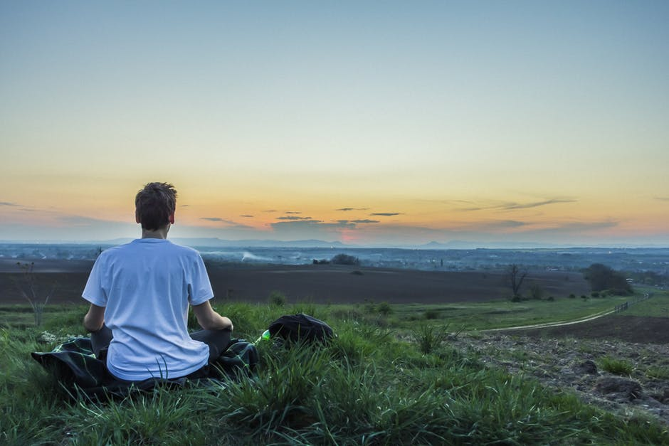 man meditating outside looking across a valley