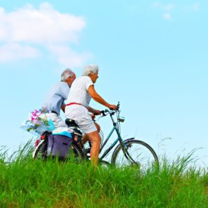 old couple cycling in countryside through grass