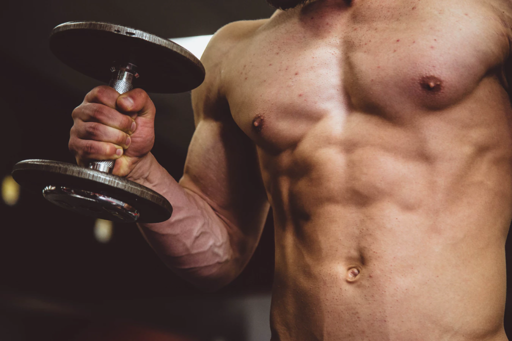 fit man with abs lifting dumbbell