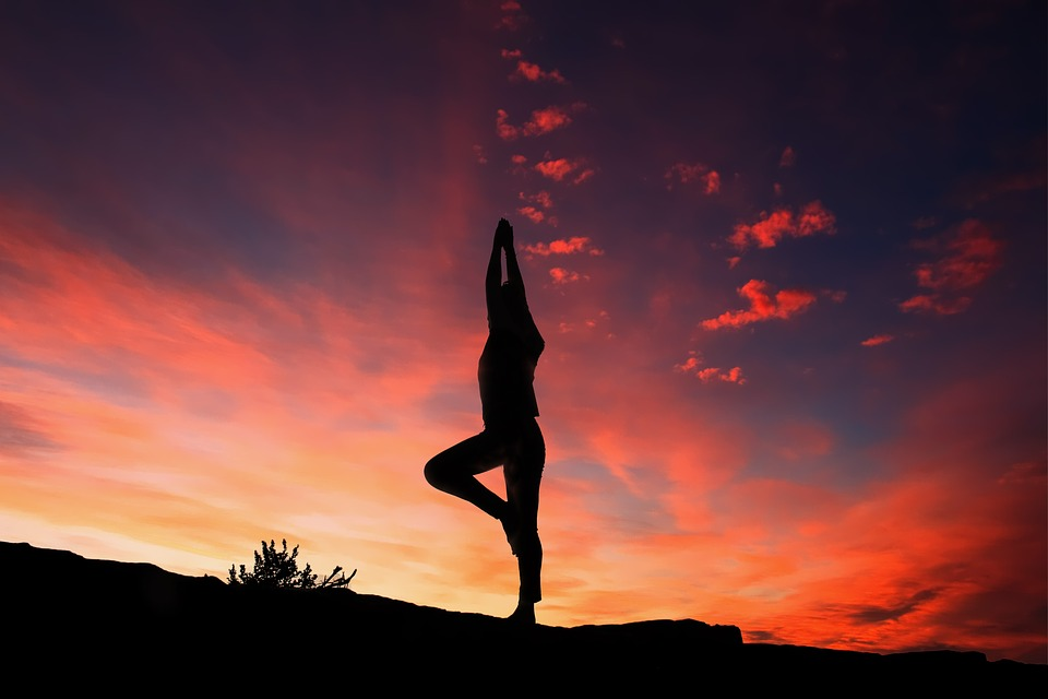woman doing yoga at sunset