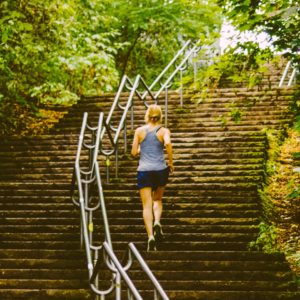 woman running up flight of steps outside