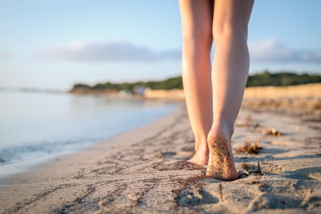 Woman walking on the beach barefoot on sand