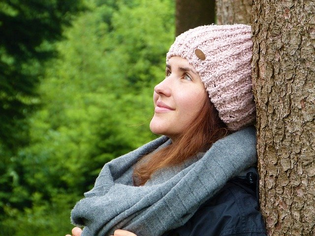 woman sitting by a tree with a woolly hat