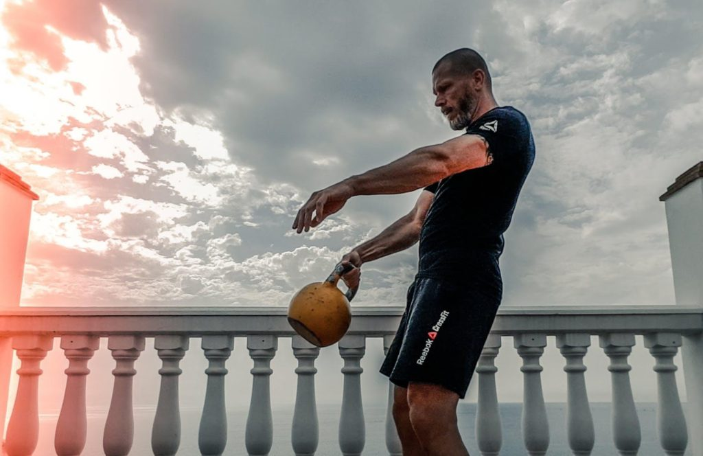 man doing kettlebell swings