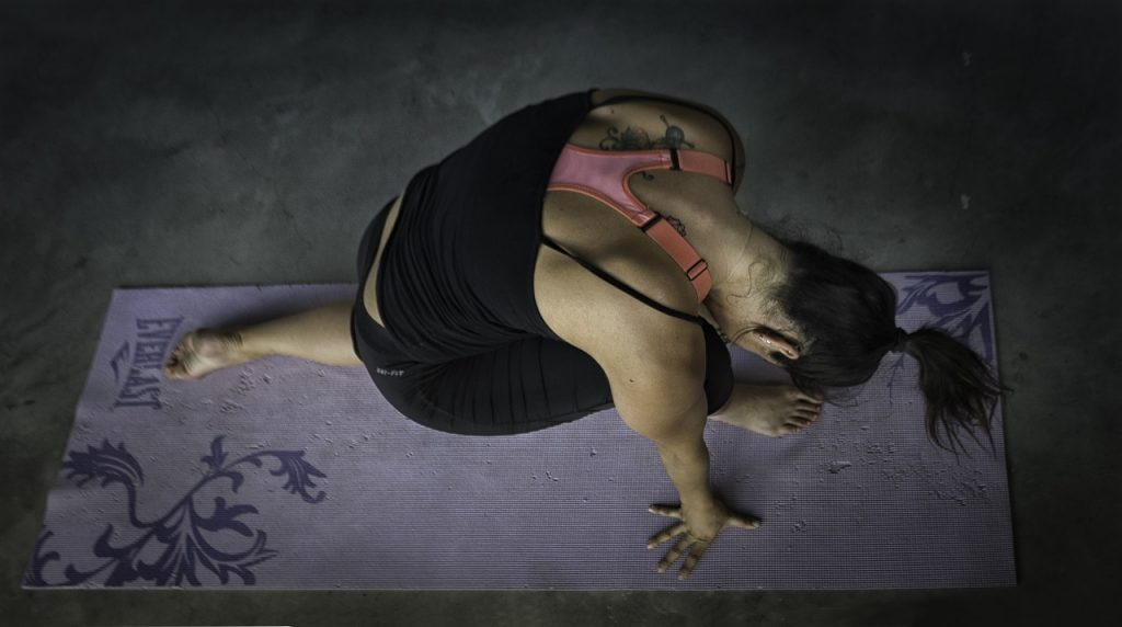 woman doing yoga on an old yoga mat