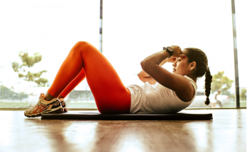 woman doing sit up crunches wearing red leggings