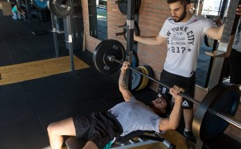 man instructing weight training in a gym